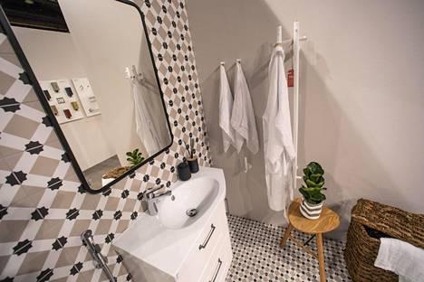 Kylppärimaailma-osastolta löytyy muun muassa tämä esimerkkikylpyhuone. Seinillä olevat laatat ovat Pukkilan Retromix-mallistosta. Kalusteet ovat Temalin, hana ORaksen, kylpyhuonetarvikkeet Tamsale Oy:n ja pyyhekuivain Rej Designin. Seinämaalina on Tikkurila Symphony x485.