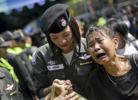 Sotilas auttoi punapaitaista mielenosoittajaa pois temppelistä.