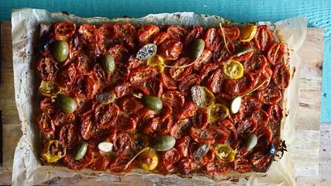 Le Marche -ravintolan tomaattipiirakka tarjoillaan usein sardellien kanssa. Tällä kertaa päälle leikataan isoja kapriksia.