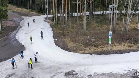 Hiihtäjiä lumetetulla ladulla Helsingin Paloheinässä 23. maaliskuuta.
