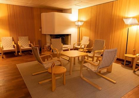 Saunan takkahuoneen nurkassa on vapaamuotoinen avotakka, jonka tulipesän ulkopinta on vaalea.