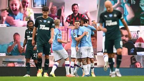 Manchester Cityn pelaajat tuulettivat digifaniensa edessä.