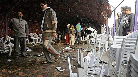 Ihmiset katselivat pommin tuhoaman juhlateltan jäänteitä.