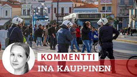 Poliisit paimensivat pakolaisia busseihin Lesboksella.