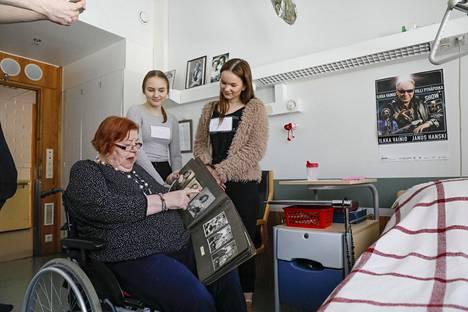 Jasmin Rentola (vas.) ja Tiina Nuutinen katsovat Toini Huolmanin nuoruuden kuvia.
