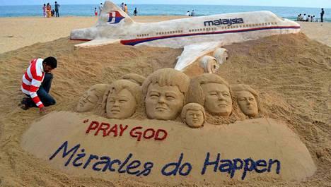 Intialaistaiteilija Sudarshan Patnaik muotoili hiekkarannalle taideteoksen ja toivoo kadonneen lentokoneen matkustajien olevan kunnossa.