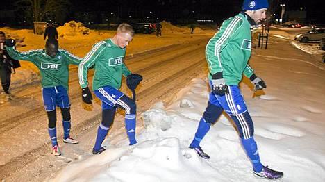 HJK:n pelaajat marssivat läpi hankien kentälle.