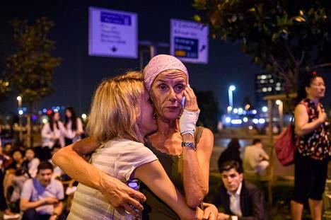 Järkyttyneitä ihmisiä Istanbulin lentokentän ulkopuolella vähän terrori-iskun jälkeen.
