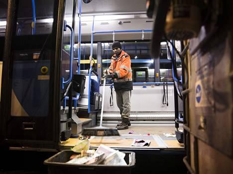 Maahanmuuttajat siivoavat busseja Espoossa.