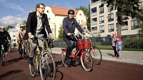 """Matti Koistinen ja Kari Karjalainen avasivat pyöräkadun pyöräilemällä. Osa juhlapyöräilijöistä ei jostain syystä noudattanut voimassa olevan tieliikennelain määräystä siitä, että pyöräilijän on """"yleensä"""" käytettävä kypärää."""