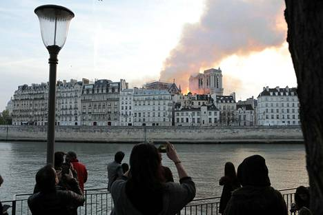 Ihmiset seurasivat Notre Damen paloa Seinen rannalla.