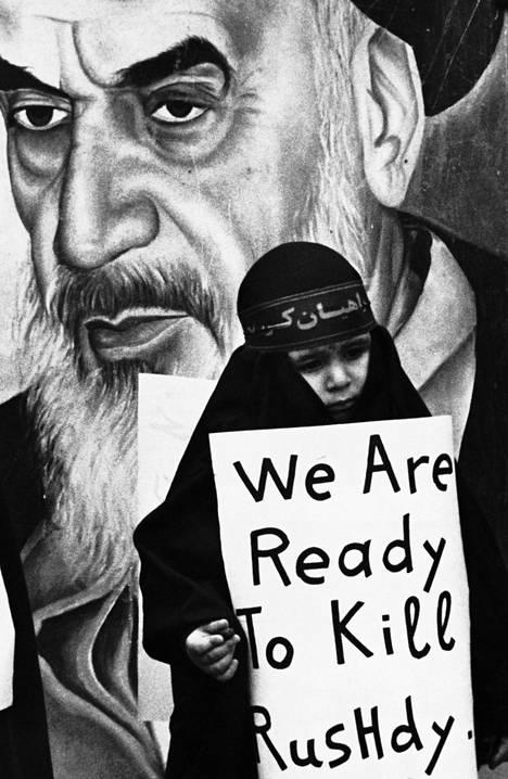 Ajatollah Ruhollah Khomeinin kuva koristi seinää, jonka edessä nuori tyttö julisti valmiutta fatwan toimeenpanemiseksi. Kuva Libanonista vuodelta 1989.