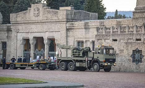 Sotilaat siirsivät arkkuja armeijan ajoneuvoihin.