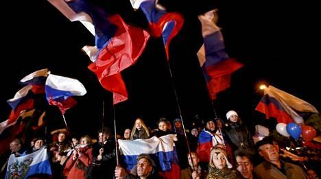 Kansan heilutti Venäjän ja Krimin lippuja Leninin aukiolla Simferopolissa.