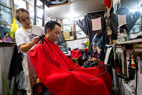 Parturi Xu leikkasi asiakkaansa hiuksia Hongkoussa Shanghaissa syksyllä 2019. Alueen talot ovat matalia, korkeintaan kaksikerroksisia jaasunnot pieniä yhden huoneen kopperoja. Omia vessoja ei ole, eikä keittiöitä. Kirjan kuvitusta.