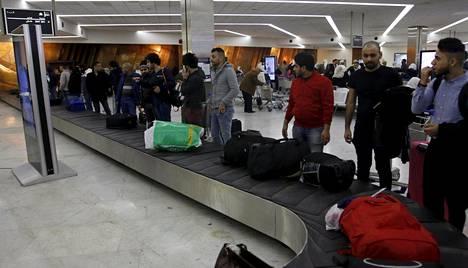 Suomesta saapuneet irakilaiset odottavat matkalaukkujaan lentokentällä.