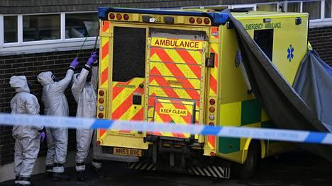 Suoja-asuihin pukeutuneet Britannian armeijan työntekijät peittivät ambulanssia pressulla Salisburyn ambulanssiasemalla lauantaina.