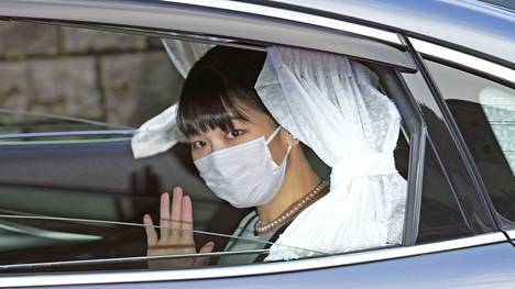 Mako vilkutti autokyytinsä sisältä valokuvaajille lähtiessään ennen häitä.