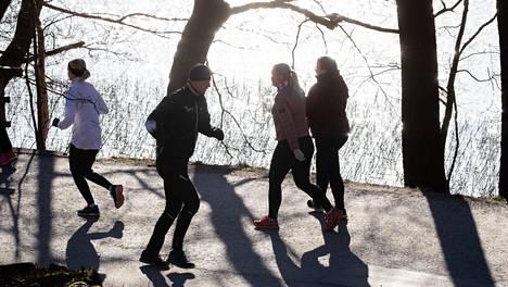 Ulkoilijoita ja lenkkeilijöitä Töölönlahdella.