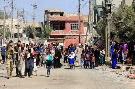 Ihmiset pakenivat taisteluita Mosulissa lauantaina.