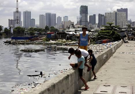 Lapsia saastuneen joen luona Manilassa, Filippiinien pääkaupungissa.