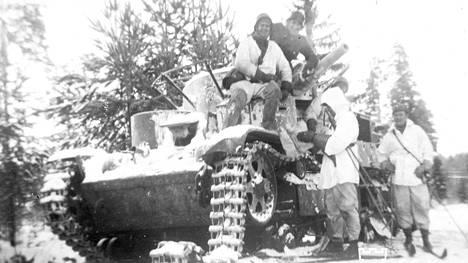 Suomalaiset tutkivat tuhottua panssarivaunua talvisodan aikana.