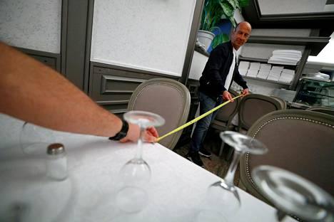 Ravintoloitsijat mittaavat pöytien välisiä suojaetäisyyksiä Nuova Fiorentina -ravintolassa Roomassa.