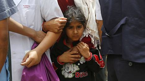 Nepalilaistyttö tarrautui äitinsä käteen kiinni, kun jälkijäristys iski perheen jonottaessa sairaalaan Kathmandussa sunnuntaina.