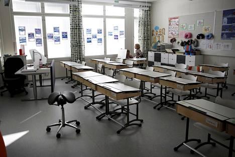 Perinteisessä koululuokassa istutaan pulpettien ääressä.