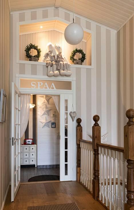 """Saunatiloihin vievän oven ylle on Sarin kotona kirjoitettu """"spa"""" suomalaisittain."""