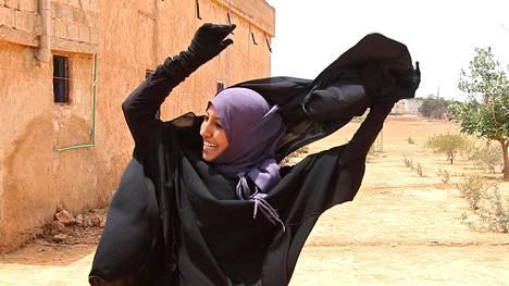 Nainen iloitsi ja riisui kasvohuntunsa Syyrian Manjibissa torstaina, kun Isisin ote kaupungista heikkeni.