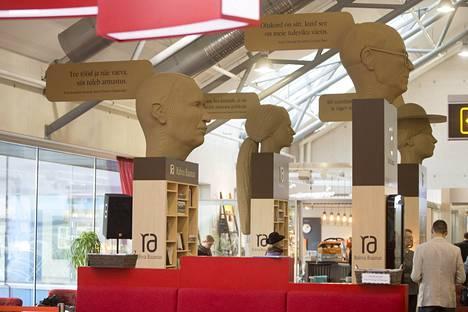 Pahvipäät on sijoitettu kirjahyllyjen päälle, joista matkaajat voivat lainata fyysisiä kirjoja tai ladata e-kirjoja lukemalla viivakoodit kirjankansien kuvista, jotka on painettu hyllyjen seiniin.