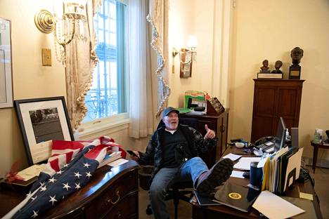 Richard Barnett poseerasi kuvaajille puhemies Nancy Pelosin työtuolilla istuen.