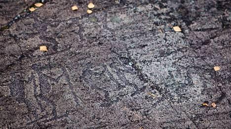 Kuvan kallioon on kaiverrettu hiihtäjiä.