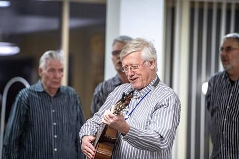 Kuoronjohtaja Matti Reittamo säestää laulajia välillä kitaralla ja välillä haitarilla.