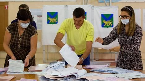 Paikallisen vaalilautakunnan jäseniä tutkimassa äänestyslomakkeita vaalihuoneistojen sulkeuduttua Vladivostokissa.
