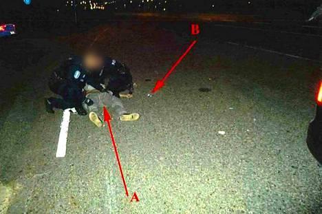 Poliisit antoivat ryöstäjälle ensiapua. B-nuolella osoitetaan painesiteen pakkausta, A-nuolella ryöstäjää.