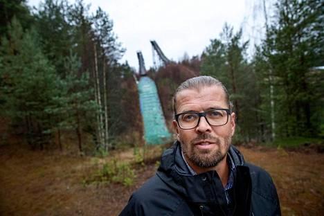 Entinen mäkihyppääjä Vesa Hakala työskentelee Harjavallan kaupungin vapaa-aikasihteerinä. Taustalla Harjavallan Hiittenharjun mäkihyppytornit vuonna 2019.