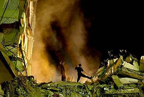 Palomiehet etsivät eloonjääneitä romahtaneen kerrostalon raunioista.