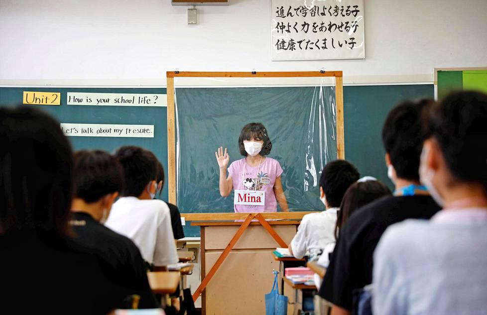 Korona-ajan koulua. Japanilainen peruskoululainen pitää englannin esitelmää kasvomaskin ja pleksilasin suojista. Tokion lähellä sijaitsevassa Takanedai Daisan koulussa on otettu kaikki keinot käyttöön koronatartuntojen ehkäisemiseksi.