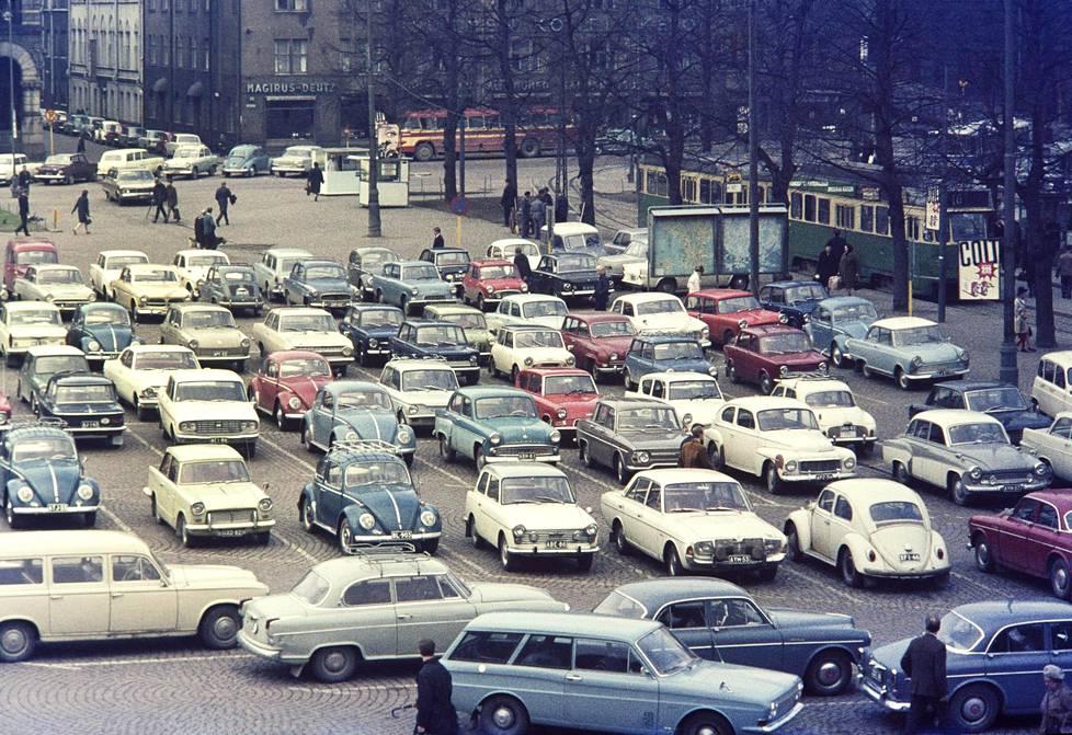 Volkkari, Pösö, Taunus, Mosse, Anglia, Triumph, Warre, Volvo, Volga, Mini, Tipparellu, Simca, Skoda… joko tuli kaikki? Rautatientori palveli parkkipaikkana 60-luvulla.