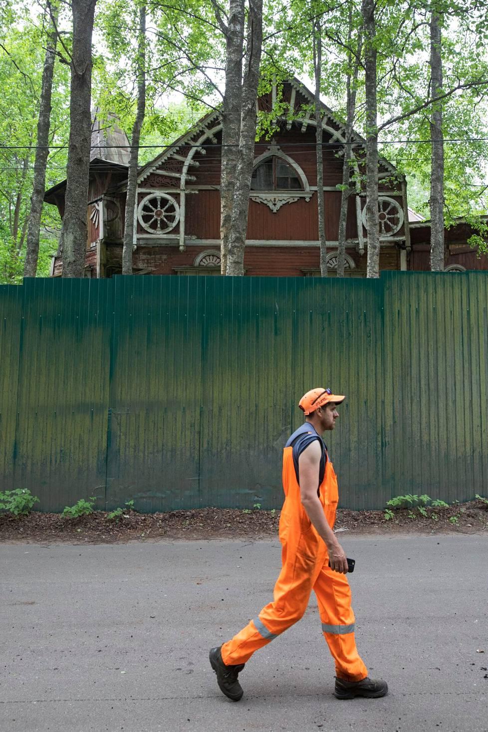 Asfaltointitöissä ollut mies kävelemässä ränsistyneen huvilan ohi.