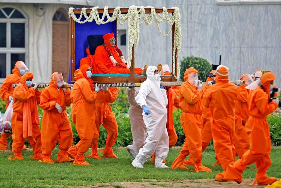 Viimeinen seremonia  Intialainen pappi Purushottampriyadasji Swamishree Maharaj sairastui covid-19-tautiin. Papin seuraajat ja terveydenhuollon henkilökunta kantoivat pappia temppeliin viimeistä seremoniaa varten. Hän menehtyi tautiin.