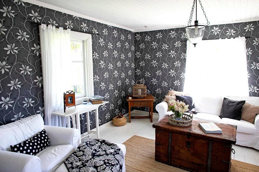 Olohuoneessa on Ikean valkoinen sohvaryhmä ja suurikuvioiset tapetit. Helteellä myös olohuone on hämmästyttävän viileä.