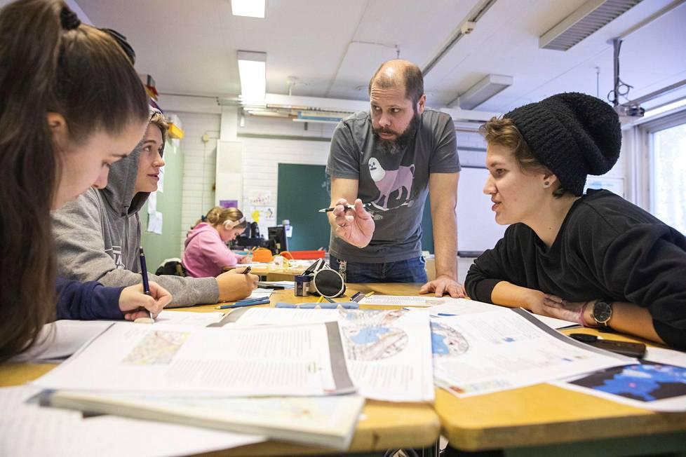 Tony Mikkola opettaa maantietoa Emilia Sibeliukselle, Vilhelm Turuselle ja Marika Laineelle Pakilan yläasteella. – Täällä on helpompi opettaa kuin Hakunilassa, Mikkola sanoo.