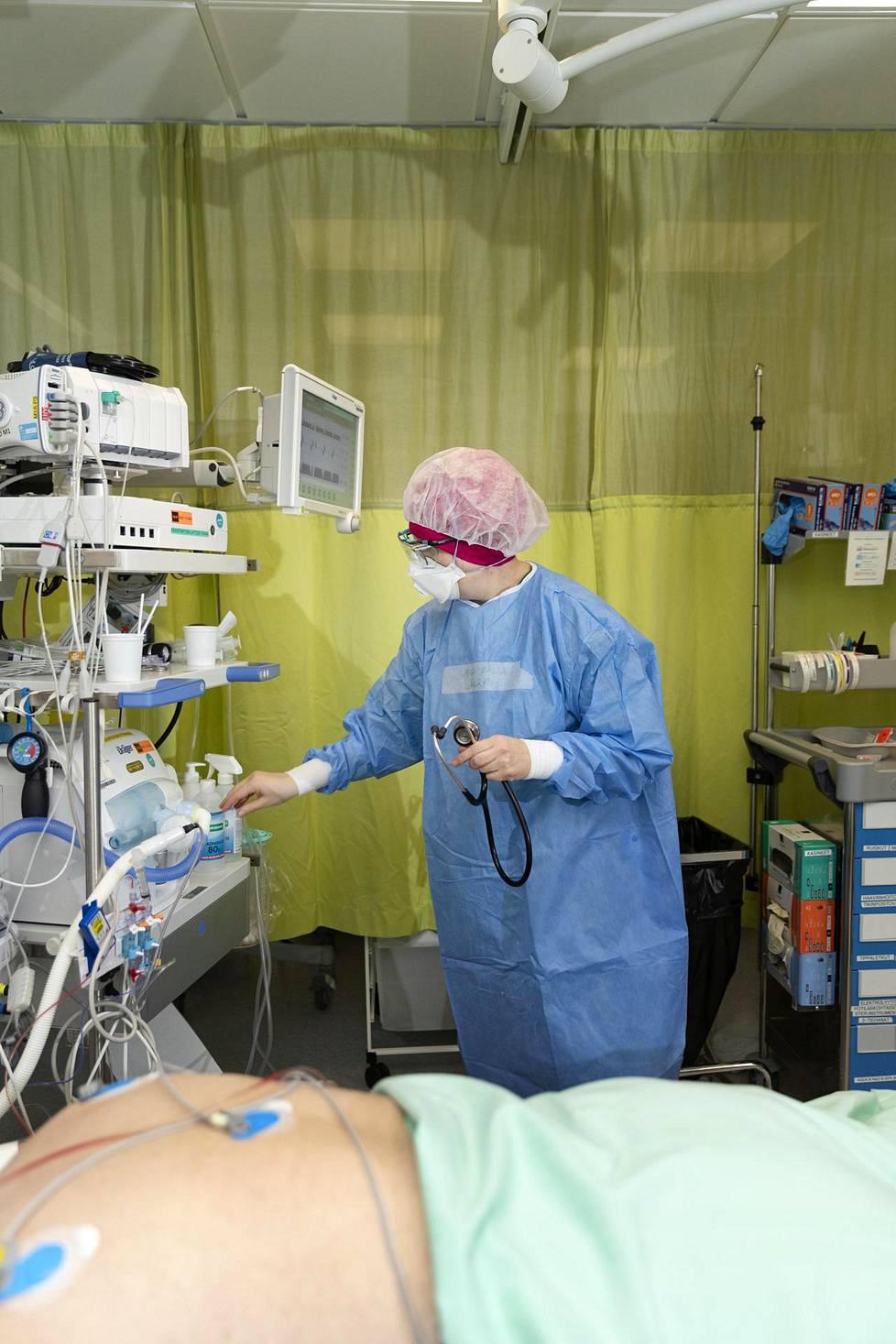Potilaaseen on kiinnitetty EKG-laitteen sensorit. Hengityskoneen yläpuolella oleva laitteisto on potilasvalvontamonitorin datayksikkö, joka kerää potilaasta kerätyn tiedon.