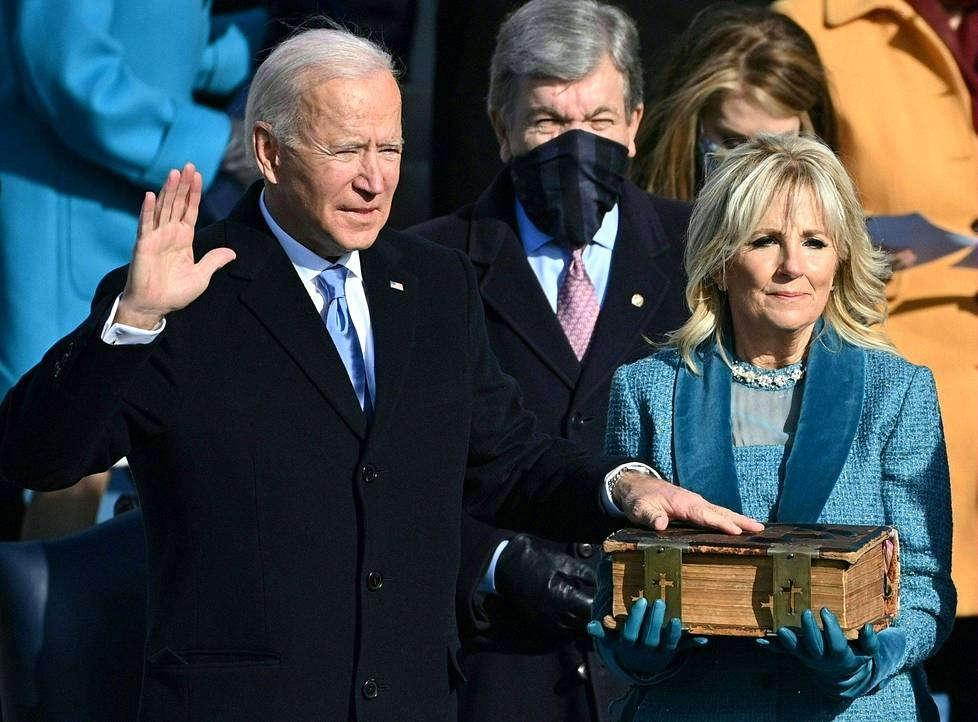 Joe Biden vannomassa virkavalaansa käsi Raamatulla, jota pitelee Jill Biden.