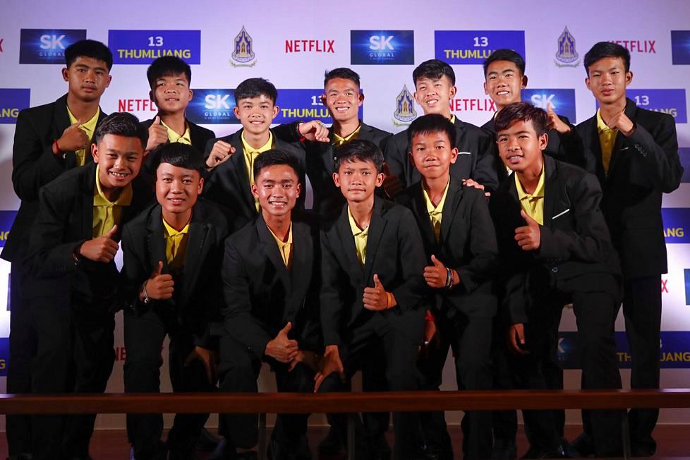 Villisiat-joukkue poseerasi kuvaajille apulaisvalmentajansa Ekapol Chantawongin (ylhäällä keskellä) kanssa Bangkokissa huhtikuussa järjestetyssä tilaisuudessa. Samassa yhteydessä kerrottiin Netflixin tulevasta elokuvasta, joka kertoo viime kesän dramaattisesta pelastusoperaatiosta.