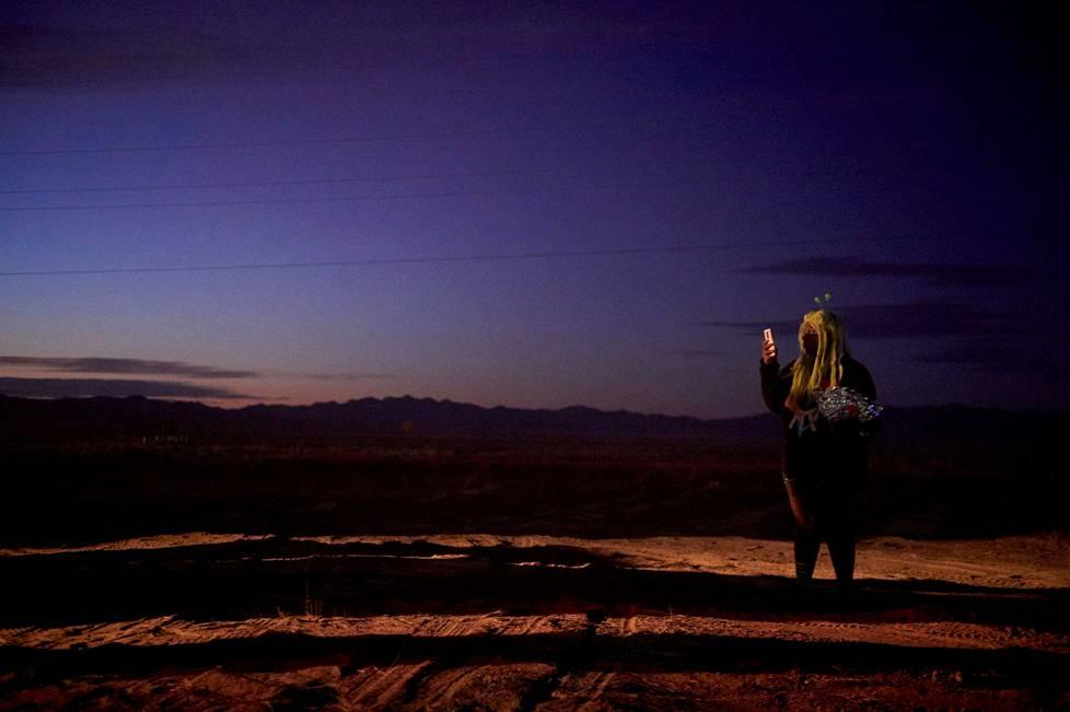 Tilaisuuteen osallistunut Phridae Lenard-Haqq tutkii puhelintaan Nevadan autiomaassa.