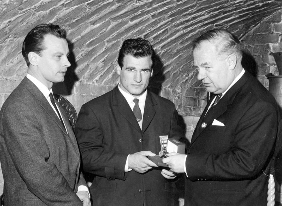 Kaarlo Kangasniemelle luovutettiin kultakello menestyksestä Tokion Olympialaisissa 1964. Vasemmalla lahjoittajan edustaja, ohjelmapäällikkö Karl Ehder ja oikealla Painonnostoliiton puheenjohtaja Bruno Nyberg.